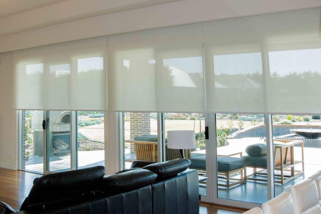 Light filtering motorised roller blinds in living room by SOM Blinds