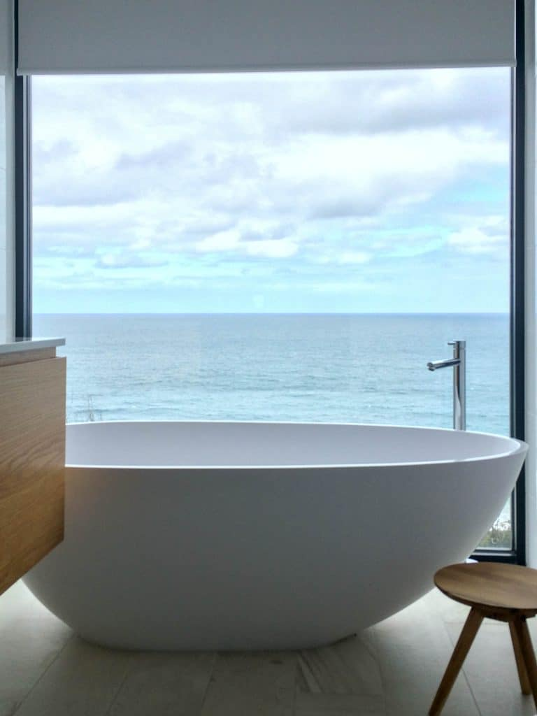 Motorised Roller blind in bathroom with seaview by SOM Blinds